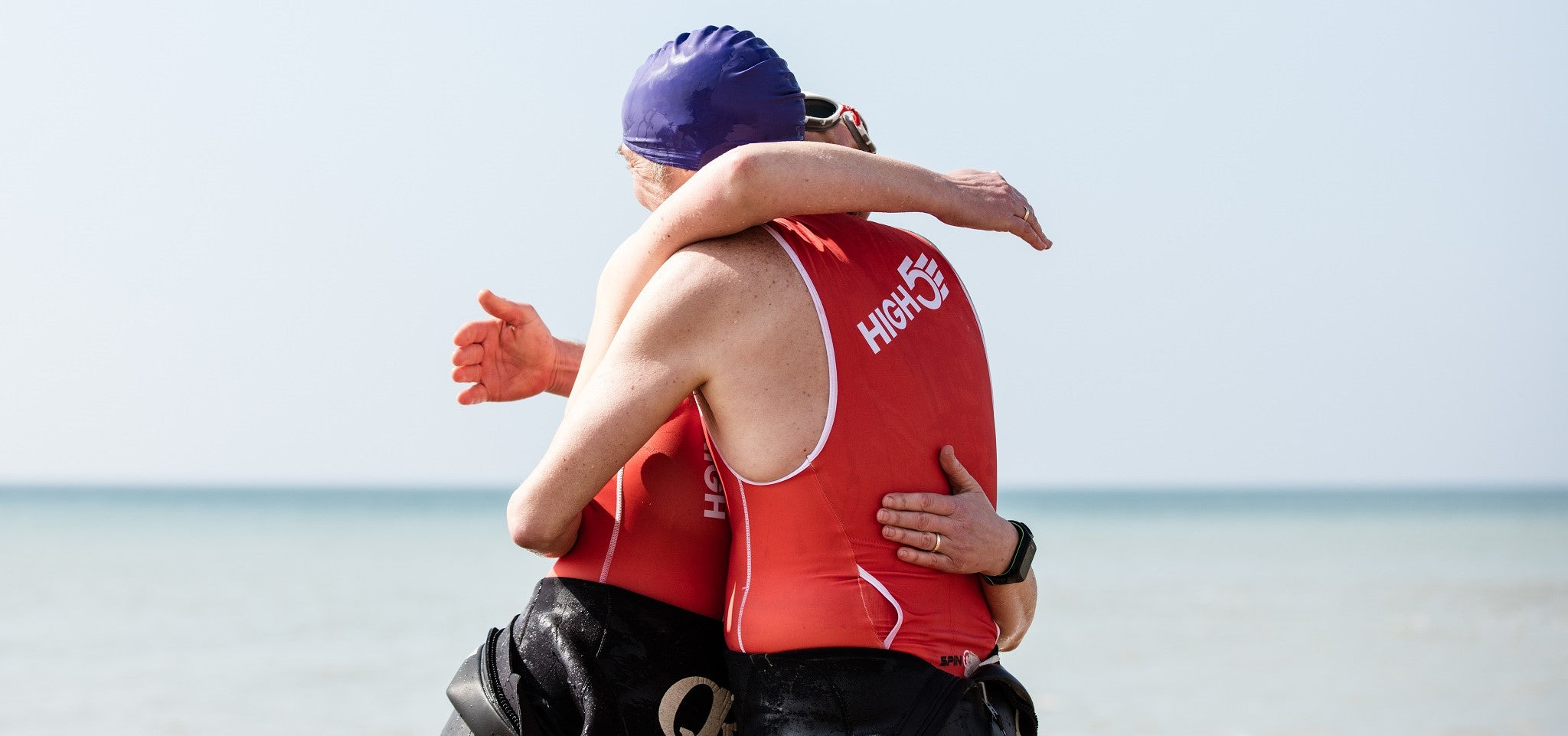 Two triathletes hugging