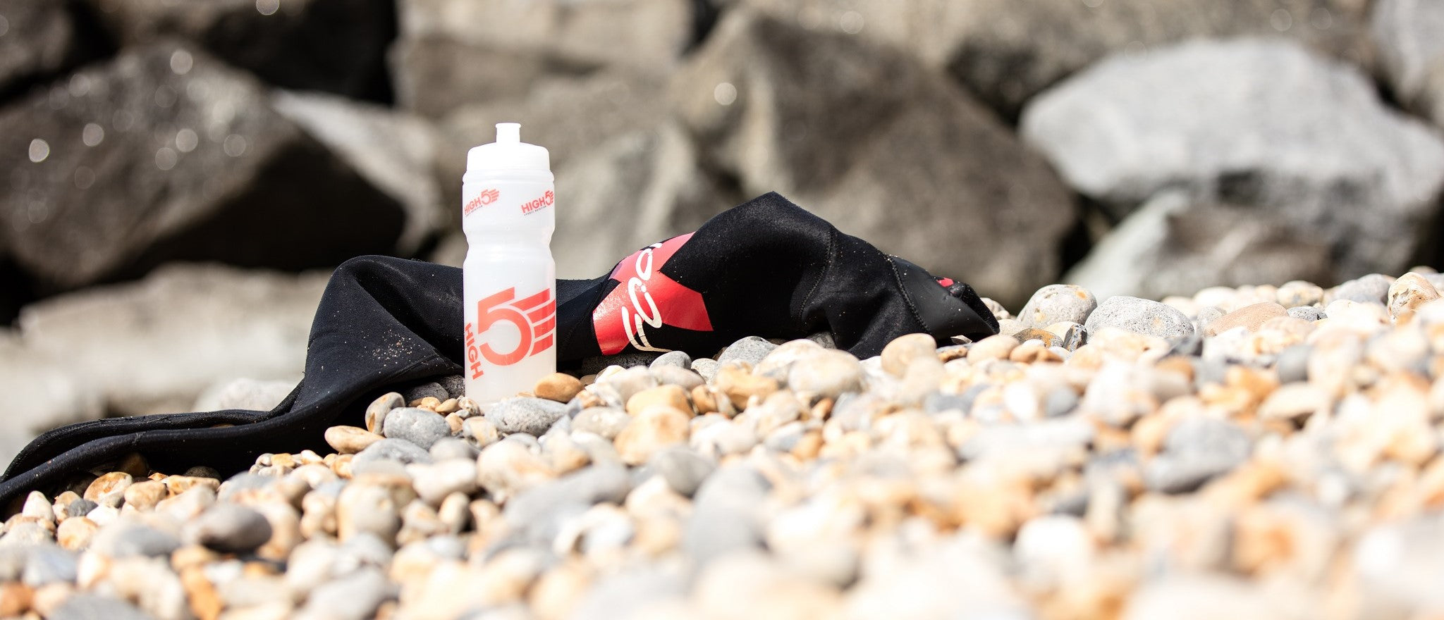 Water bottle and wetsuit on a beach