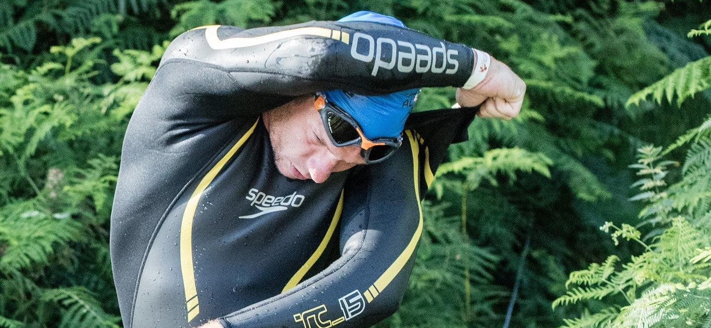 Man removing a wetsuit during a triathlon