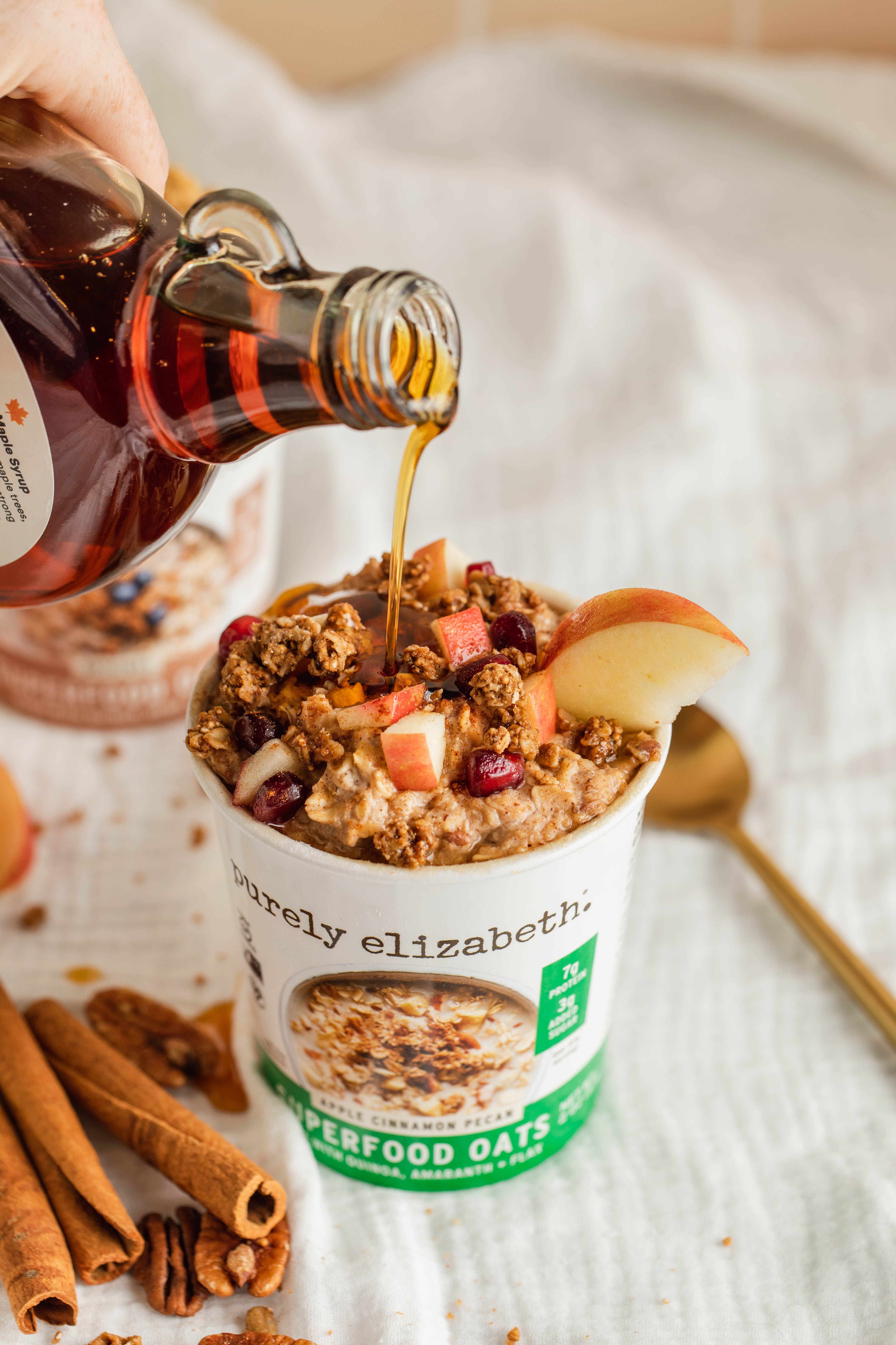 Maple syrup poured over Apple Cinnamon Superfood Oats