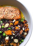 Traditional Italian salmon meal, An oven-baked salmon fillet rolled over a bed of aromatic herbs chop, served with butternut squash, French peas, sage flavoured Venere black rice and a sprinkle of crushed roasted almonds.