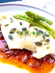 Italian Sicilian traditional recipe. A premium oven cooked cod fillet, served on a bed of Hermes brown rise and crunchy asparagus, with a sprinkle of pumpkin seeds.