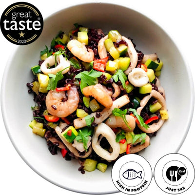 Italian seafood risotto, healthy and high in protein. A unique risotto made with Venere black rice, calamari, king prawns, zucchini, flavoured with fresh parsley, lemon zest and crushed almonds.