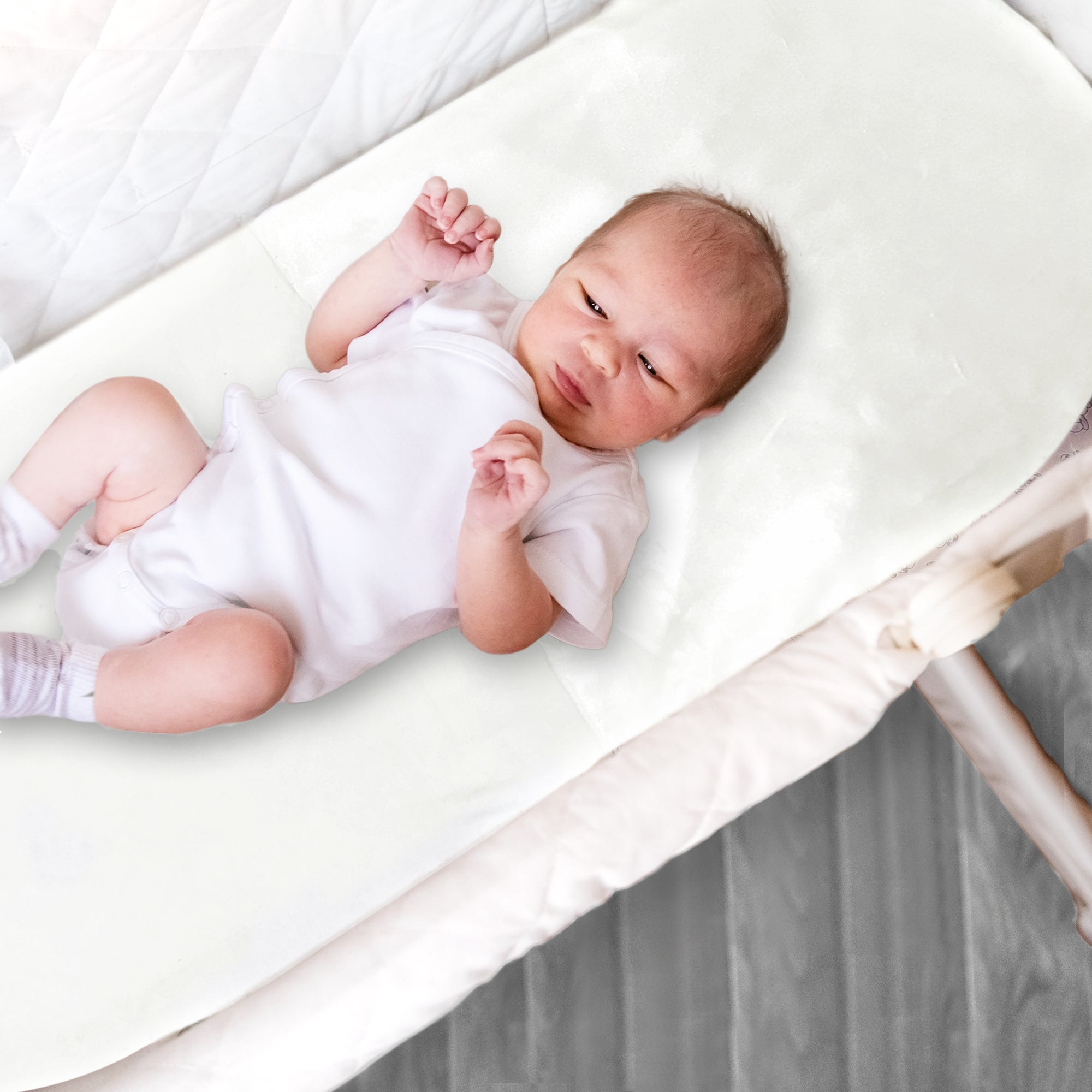 Baby laying in a Moses basket featuring a fitted satin sheet