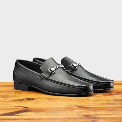 Pair of 8616-M Calzoleria Toscana Black Buff Calf Slip-On on top of a wooden table
