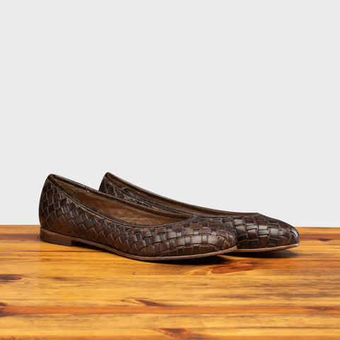Pair of B940 Calzoleria Toscana Tobacco Woven Melania Ballerina Flat on top of a wooden table