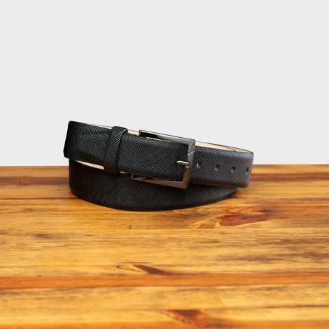 Front profile of  C1499 Calzoleria Toscana Black Saffiano Leather Belt curled on top of a wooden table