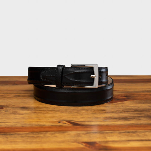 Front profile of C2216 Calzoleria Toscana Black Inner Stitched Dress Belt curled up on top of a wooden table