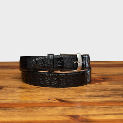 Front profile of C7981 Calzoleria Toscana Black Exotic Hornback Belt on top of a wooden  table