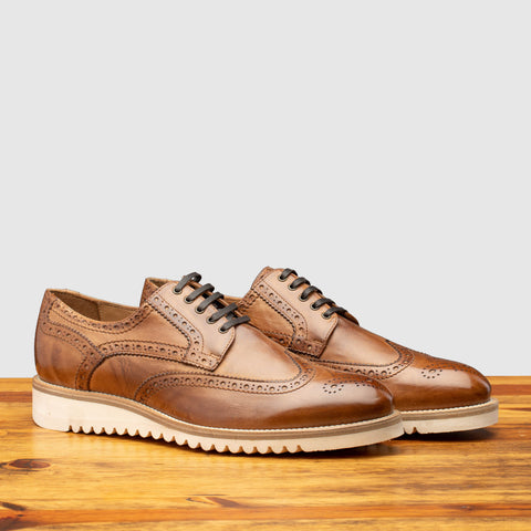 Pair of Q399 Calzoleria Toscana Cerris Agos Wingtip Blucher on top of a wooden table