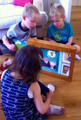Two boys are reading the gingerbread man kamishibai, which is in a wooden frame on the floor, to a younger girl