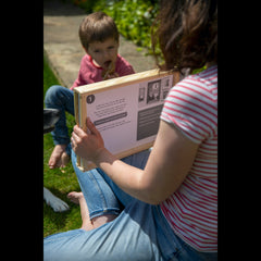 A mum holds the gingerbread man kamishibai story in a frame and is reading to her son who is facing her eating a gingerbread man biscuit