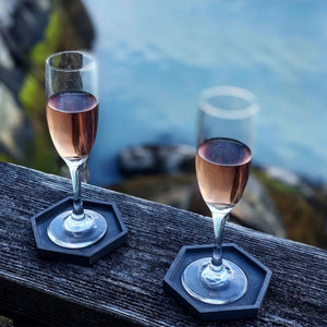 two champagne glasses on octagon coaster in front of lake