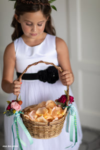A girl in Blooma flower girl dress with a busket of petals