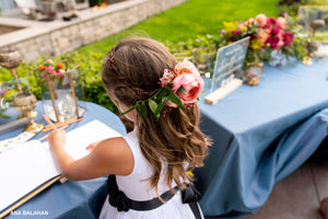 Flower girl in Bluma dress signing a wedding guest book