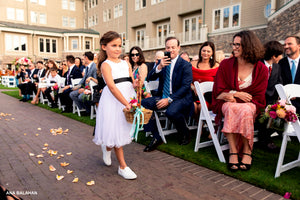 Flower girl in white Bluma dress with navy floral sash walking down the aisle throwing petals