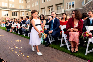 Flower girl walking down the aisle throwing petals in Adelina dress by Ana Balahan