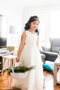 Flower girl wearing Grace Vneck ivory dress with basket of flowers