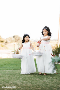 Two flower girls walking down the aisle throwing petals