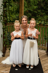 Bride hugging two girls with flower baskets
