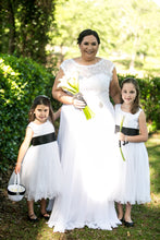 Load image into Gallery viewer, Bride with two flower girls in Adelina white color dresses with wave edge and black color sashes Ana Balahan