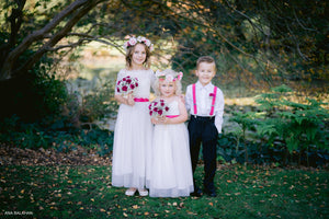 Two junior bridesmaids in their long dresses with lace tops and floral summer rose wreaths and page boy wearing matching accessories.