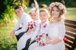 Flower girls and page boys in their special occasion outfits with floral wreath and bouquets. Beautiful garden wedding.
