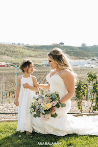 Bride and flower girl with wedding bouquet at a winary wedding