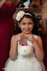 Flower girl with a basket of petals wearing Camellia set of wedding accessories floral sash and headpiece