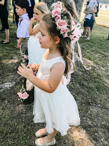 Girl in Adelina ivory color dress with flower wreath