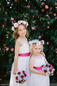 Girls are wearing Scarlett flower girl dresses with spagetti straps with magenta sashes and floral wreath