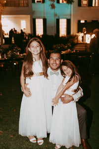 Groom with two flower girls wearing comfortable ivory Grace dresses