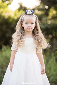 Girl in Sofia champagne lace flower girl dress with floral headpiece