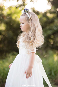 Girl in Sofia champagne lace flower girl dress with floral headpiece side view