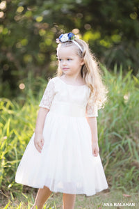 Girl in medium length Sofia champagne lace flower girl dress with flower headpiece