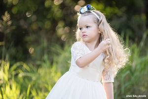 Girl wearing Sofia champagne lace flower girl dress