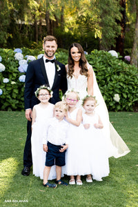 Beautiful bride and groom with flower girl in Grace V-neck dress