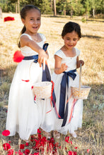 Load image into Gallery viewer, Two cute flower girls in Annabelle dresses with navy sashes throwing petals