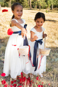 Two cute flower girls in Annabelle dresses with navy sashes throwing petals
