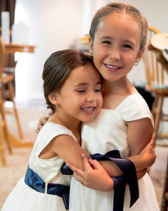 Two cute hugging flower girls in Annabelle dresses with navy sashes