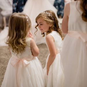 Two pretty girls in Adelina ivory color dresses and blush color sash Ana Balahan