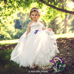 A cute girl in a lush Snow Cloud flower girl dress by Ana Balahan in a park