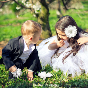 Boy in stylish gentlemen suit picking flowers with a flower girl