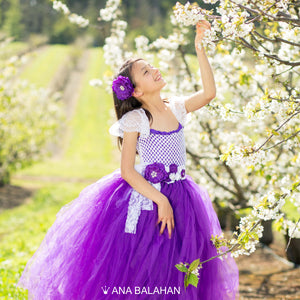 Beautiful girl in whate and purple tutu dress with floral accessories