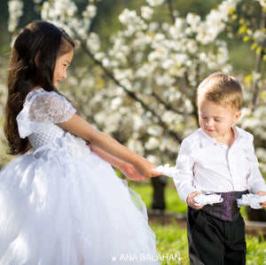 Cute girl in white jasmine blossom tutu dress and handsome boy in smart suit watching a flower