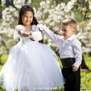 Cute girl in white jasmine blossom tutu dress and handsome boy in smart suit