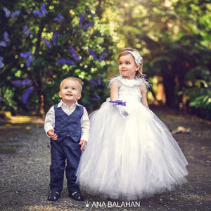 Boy in a fashionable suit and a flower girl looking at butterflies