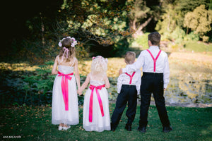 Kids wearing special ocassion wear and set of wedding accessories suspenders page boy bow ties flower girl sashes and headpieces