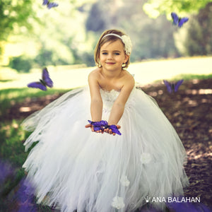 A cute girl wearing Snow Cloud flower girl dress holding butterflies