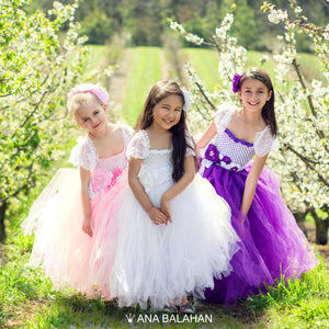 Three girls in tutu dresses at a cherry orchard